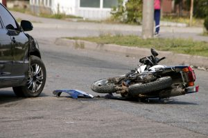 A motorcycle lies damaged on the road next to a damaged car.